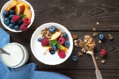 Yogurt with Granola  and fresh berries. On  wooden table. Healthy breakfast Royalty Free Stock Photo