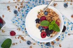 Yogurt with Granola and fresh berries. On wooden table. Healthy breakfast Stock Images