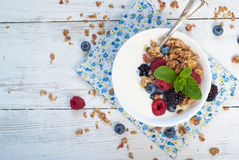 Yogurt with Granola and fresh berries. On wooden table. Healthy breakfast Royalty Free Stock Images