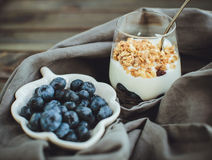 Yogurt with granola and fresh blueberries, in glass bowl over ol Stock Images