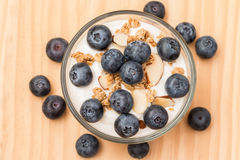 Yogurt with granola and organic blueberries in glass bow. Royalty Free Stock Photos