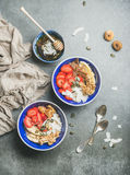 Yogurt, granola, seeds, fruits and honey in blue ceramic bowls Royalty Free Stock Photo