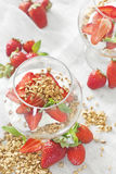 Yogurt with granola and strawberry. Natural yogurt with homrmade granola and ripe strawberry in the glass goblets. High key Royalty Free Stock Image