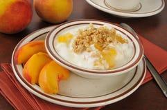 Yogurt greco con le pesche ed il granola Fotografia Stock