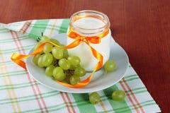 Yogurt and green grapes Stock Photo