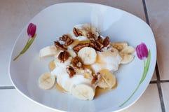 Yogurt honey and walnuts. Plate with honey walnut yogurt and banana slices Royalty Free Stock Photo