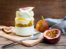 Yogurt jar with passion fruit and fresh fig. Yogurt jar with passion fruit and fresh fig for healthy breakfast or clean food concept Royalty Free Stock Photo