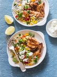 Yogurt marinated grilled chicken breast and israeli couscous and vegetables tabouli salad on a blue background Royalty Free Stock Photos