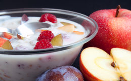 Yogurt mixed with fruit pieces. Glass bowl filled with yogurt mixed with fruit pieces arranged with spoon and some fruits around Stock Images