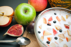 Yogurt mixed with fruit pieces. Glass bowl filled with yogurt mixed with fruit pieces arranged with spoon and some fruits around Stock Photos