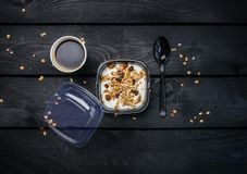 Yogurt with muesli and coffee in a disposable container. Top view dark wooden background Royalty Free Stock Photos