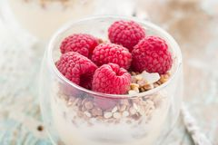 Yogurt with muesli and fresh raspberries. Breakfast with muesli, yogurt and fresh raspberries Royalty Free Stock Photography