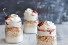 Yogurt with muesli and strawberry on a wooden table Stock Images