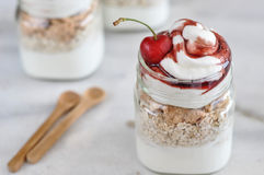 Yogurt with muesli and strawberry on a wooden table Royalty Free Stock Image