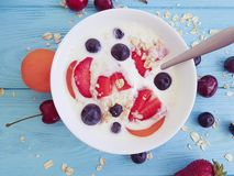Yogurt,natural oatmeal, gourmet  strawberries, blueberries on a wooden background. Yogurt natural  oatmeal, strawberries blueberries on a wooden background royalty free stock photography