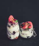 Yogurt and oat granola with grapes, pomegranate, grapefruit in tall glass jar Royalty Free Stock Photos