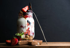 Yogurt oat granola with strawberries, mulberries, honey and mint leaves in tall glass jar on black backdrop Royalty Free Stock Image