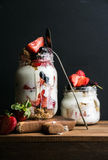 Yogurt oat granola with strawberries, mulberries, honey and mint leaves in tall glass jar on black backdrop Stock Photo