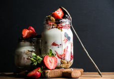 Yogurt oat granola with strawberries, mulberries, honey and mint leaves in tall glass jar on black backdrop Royalty Free Stock Images