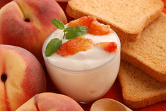 Yogurt with peach flavor. Decorated with mint leaves royalty free stock image