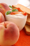 Yogurt with peach flavor. Decorated with mint leaves stock images