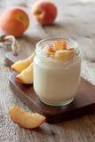 Yogurt with peach in a glass jar Stock Photos
