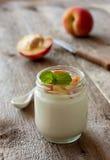 Yogurt with peach in a glass jar Royalty Free Stock Photos
