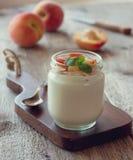Yogurt with peach in a glass jar (Toning) Stock Photo