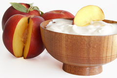 Yogurt with peaches. In a wooden bowl stock image