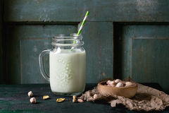Yogurt with pistachios. Drinking yogurt with pistachios served in glass mason jar with cocktail tubes and bowl of nuts on old wooden table. Dark rustic style stock photos