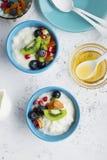 Yogurt, porridge del latte, granola per la prima colazione con bacche differenti, dadi e frutti: kiwi, melograno, albicocche secc immagine stock libera da diritti