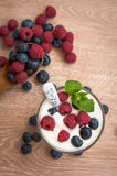 Yogurt with raspberries and blueberries. Tender, delicious, diet white yogurt with raspberries and blueberries on the table Stock Photography