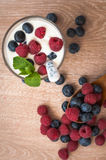 Yogurt with raspberries and blueberries. Tender, delicious, diet white yogurt with raspberries and blueberries on the table Stock Photos