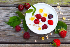 Yogurt with raspberries, strawberries and sour cherries. Homemade yogurt with raspberries, strawberries and sour cherries, with grain cereals flakes on a wooden Stock Photo