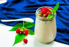 Yogurt with raspberry berries and muesli, decorated with mint leaves, in a small glass jar on a white table with a blue tablecloth. Copy space stock photography