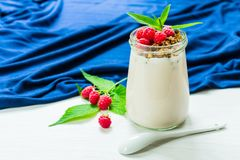 Yogurt with raspberry berries and muesli, decorated with mint leaves, in a small glass jar on a white table with a blue tablecloth. Copy space stock photo