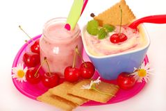 Yogurt and rice pudding with cherry for baby. Jar with  cherry yogurt ,bowl of rice pudding  and biscuits as baby food Stock Photos