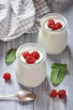 Yogurt with ripe fresh raspberry. In jars on wooden background Stock Photography