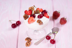 Yogurt with strawberries and cherries and walnuts in a glass bowl. Royalty Free Stock Photos
