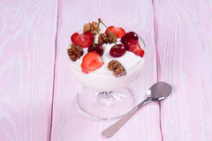 Yogurt with strawberries and cherries and walnuts. Stock Photography