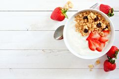 Yogurt with strawberries & granola, flat lay, side orientation over white wood. Bowl of yogurt with strawberries and granola, over a white wood background Stock Photography