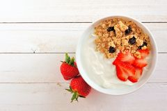 Yogurt with strawberries and granola over white wood. Bowl of yogurt with strawberries and granola, over a white wood background. Flat lay Stock Photo