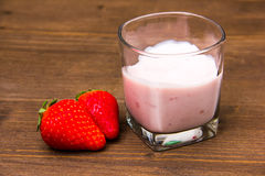 Yogurt with strawberries on wood Stock Images