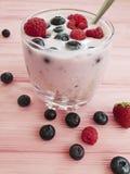 Yogurt, strawberry, raspberry, blueberries on a pink wooden background,. Yogurt strawberry raspberry blueberries on a pink wooden background Royalty Free Stock Photo
