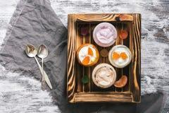 Yogurt su un vassoio di legno, tovagliolo, cucchiai, fondo rustico bianco della prima colazione Vista superiore Immagini Stock Libere da Diritti