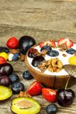 Yogurt with summer fruit on an old wooden table. Fruit refreshment. Snack for children. stock image