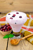 Yogurt thick with cranberries and spoon on the board Royalty Free Stock Photos