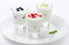 Yogurt tre con frutta in un orizzontale di vetro del becher Fotografie Stock Libere da Diritti
