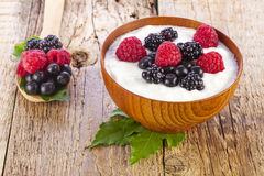 Yogurt with wild berries in wooden bowl on wood Royalty Free Stock Image