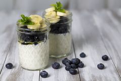 Yogurt wit blueberries & sliced bananas. In a glass jar, topped with honey and mint stock images